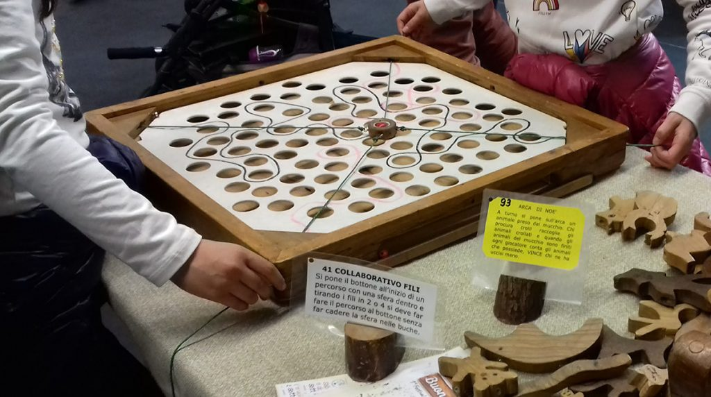 Giochi in legno - il labirinto cooperativo in cui tirando in modo coordinato dei fili bisogna far muovere una pallina lungo un percorso senza farla cadere nei buchi