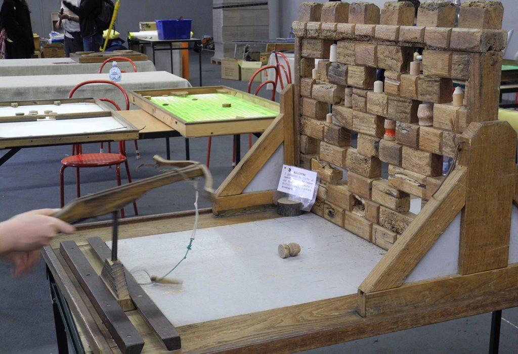 Giochi in legno - un muro di tappi da buttare giù con la balestra