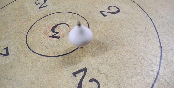 Giochi in legno - trottola in legno che gira sulla pista tra i punteggi 2 e 3
