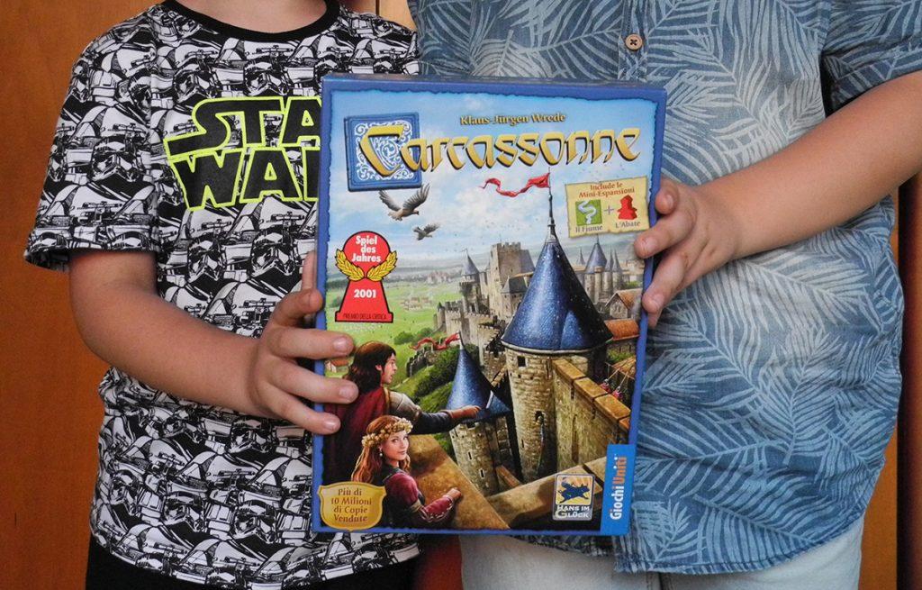 La scatola del gioco Carcassonne retta da due bambini