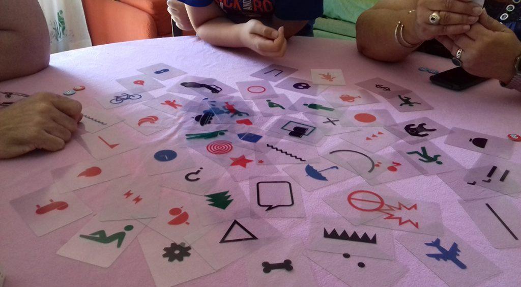 Davide, il papà e la nonna intorno al tavolo su cui si trovano le carte trasparenti per giocare a Imagine