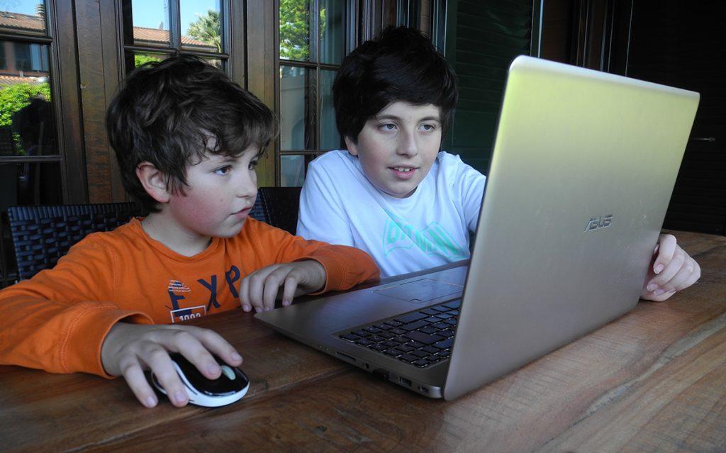I bambini davanti al computer per una partita a un gioco virtuale da tavolo con gli amici lontani