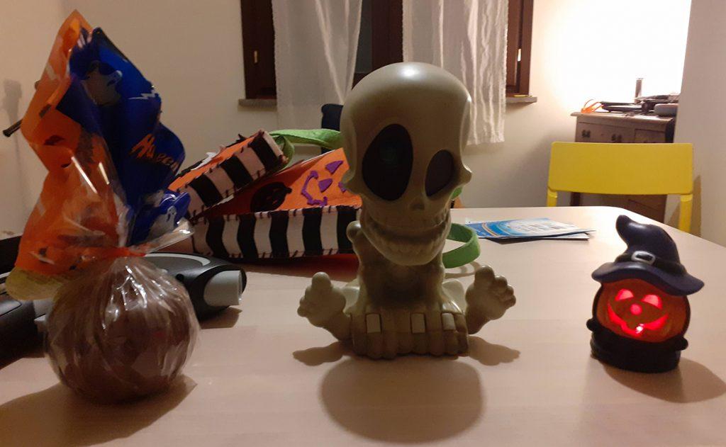 In primo piano sul tavolo circondato da decorazioni di Halloween lo scheletro che proietta fantasmi in tutta la stanza
