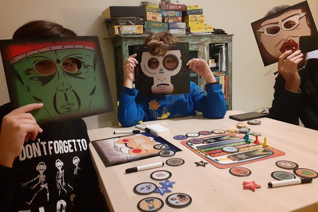 """""""Serie TV"""" - papà e bambini attorno al tavolo da gioco con la maschera davanti al viso"""