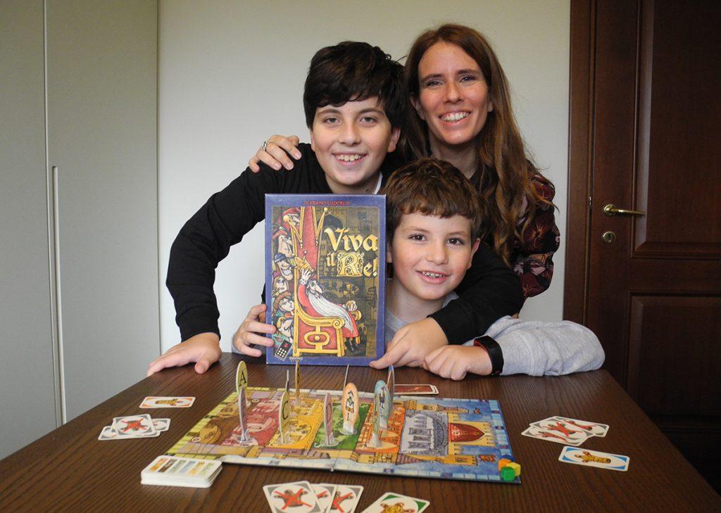 Mamma e bambini con la scatola di Viva il Re! e il gioco pronto sul tavolo per iniziare una partita