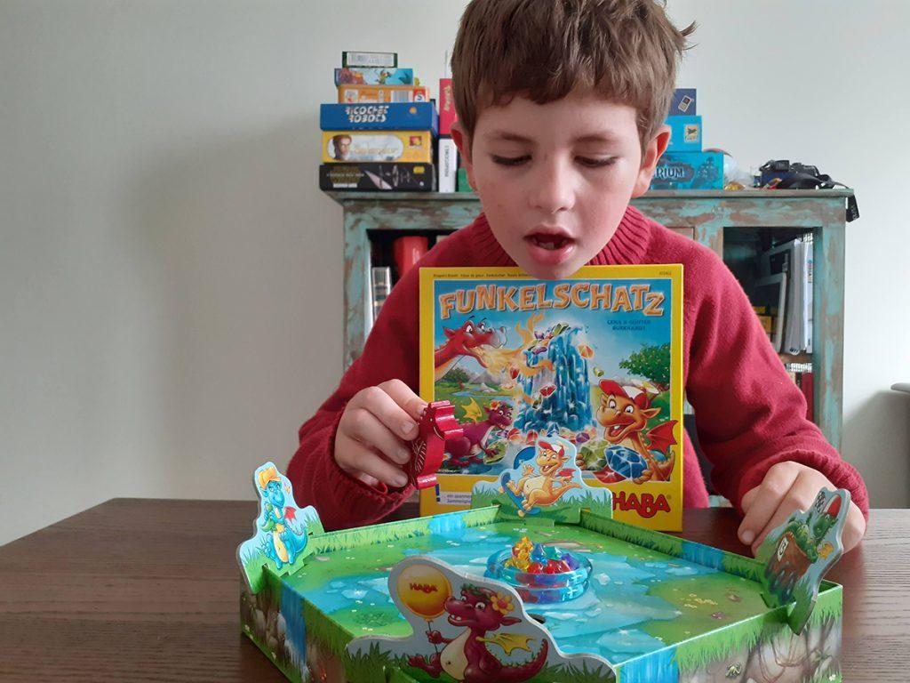 Lorenzo con la scatola di Funkelschatz e il gioco aperto davanti a sé