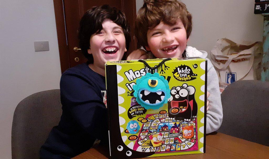 """Davide e Lorenzo sorridenti con la scatola di """"Mostri in Fuga"""" Lisciani"""