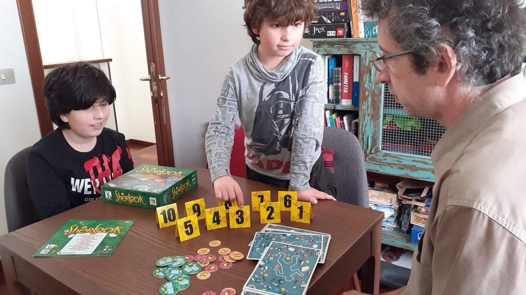 """Carlo e i bambini stanno finendo di sistemare sul tavolo i pezzi di """"Sherlook"""", uno dei nostri giochi di osservazione preferiti"""