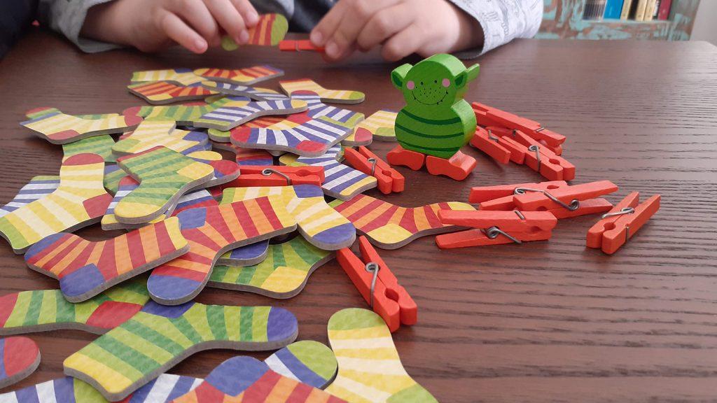 """Giochi di osservazione: i pezzi del gioco di """"Rubacalzini"""" sono calzini, mollette e il pupazzetto del mostro dei calzini."""