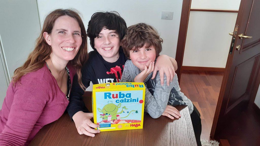 """Claudia, Davide e Lorenzo seduti con la scatola del gioco """"Ruba calzini"""", uno dei giochi di osservazione più adatto per i più piccoli"""