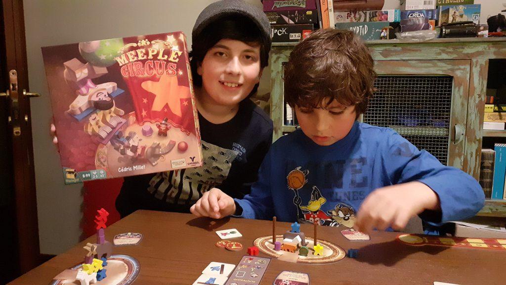 Davide tiene in mano la scatola del gioco di Meeple Circus mentre Lorenzo finisce di comporre la sua esibizione