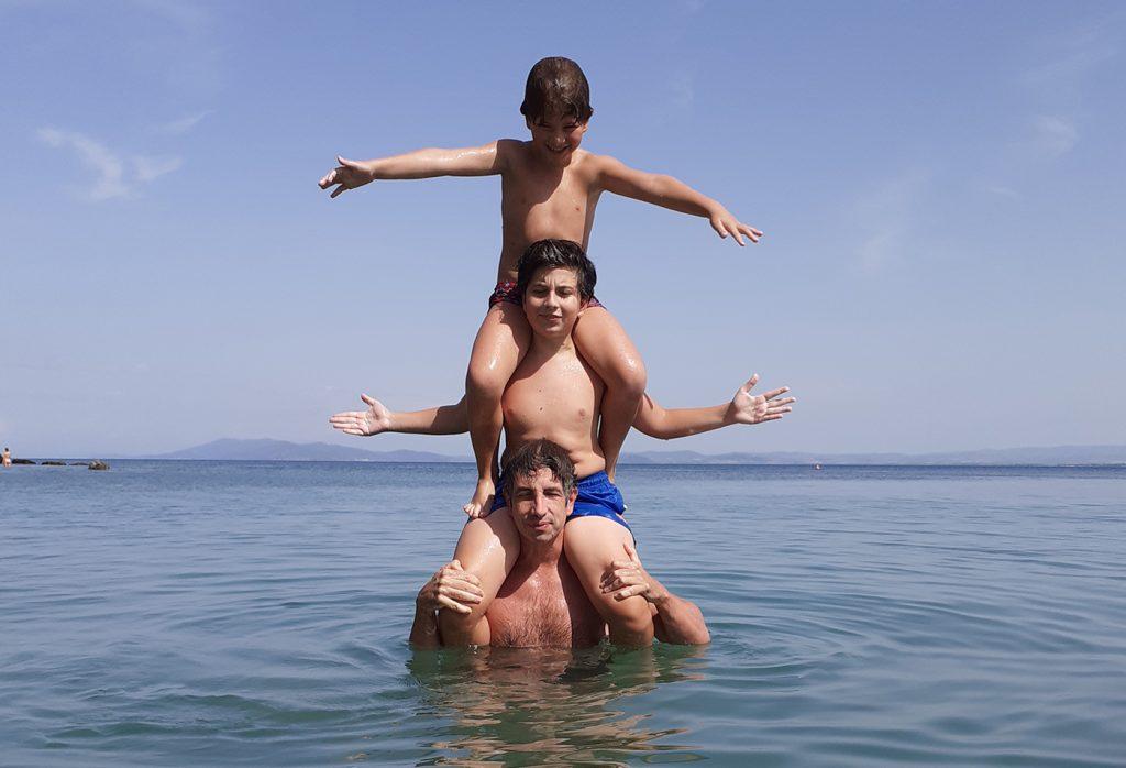 In acqua al mare, torre di bambini sopra al papà