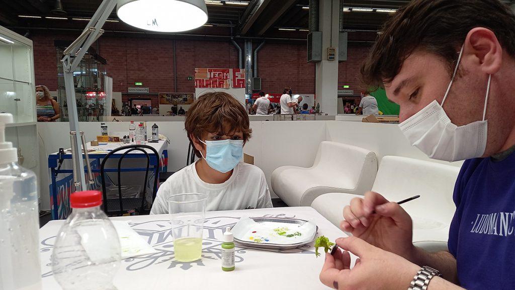 Lorenzo dipinge una miniatura ad un laboratorio di Ludomaniacs insieme a Davide, uno degli artisti dell'associazione